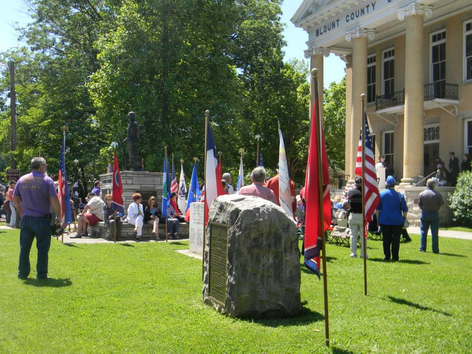 Image of grounds of Court House, with flags in stakes and attendees milling about